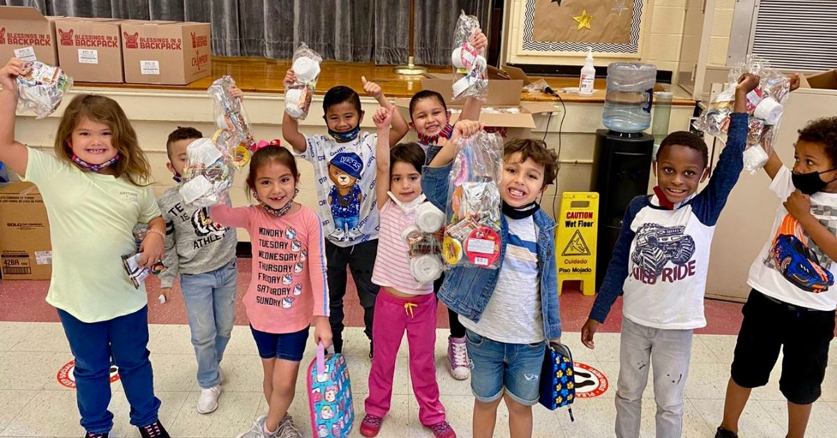 Kids holding up bags of food